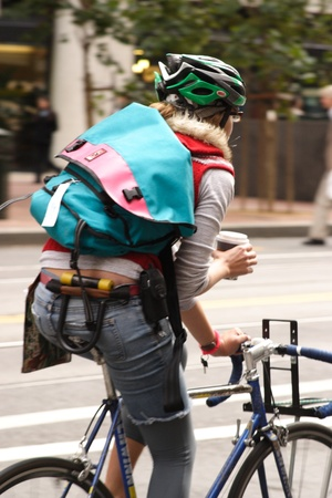 road bike: Female cyclist in trendy attire with a cup of coffee riding on city street