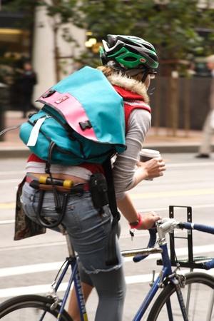 Vrouw fietser in trendy kleding met een kopje koffie rijden op straat in de stad Redactioneel