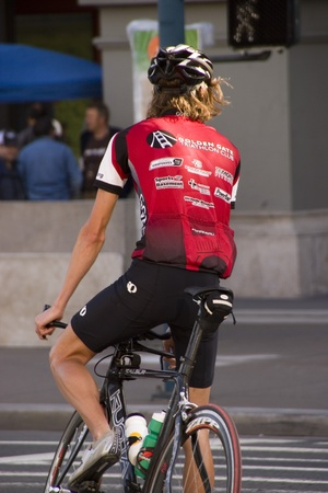 road cycling: cyclist in red jersey at waiting to cross the street
