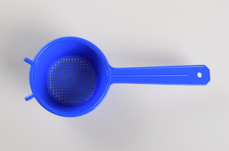 Blue plastic tea strainer isolated on white background