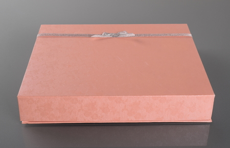 finer: Decorated box on gray background. Carrot color