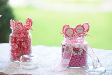 Bonbons roses et blancs en pot de verre à la fête ou à la célébration de mariage Banque d'images - 75565871
