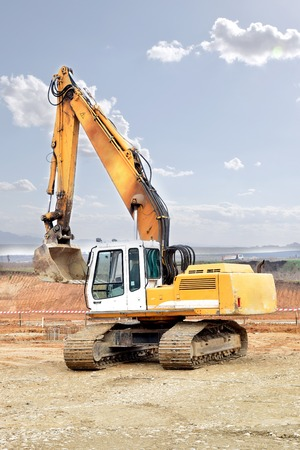 Excavator digging and moving earth at construction site