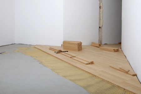 renovated: Construction in a renovated room installation of parquet.Pad applied with glue for parquet Stock Photo