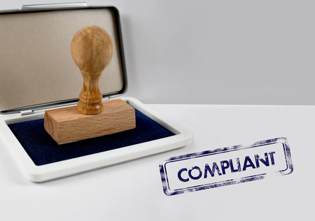compliant: Wooden stamp with ink on desk COMPLIANT Stock Photo