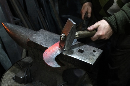 Blacksmith with hammer working on a heated iron sickle in workshop Imagens