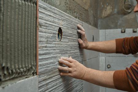 Pegado de azulejos en la pared. Colocación de azulejos en la pared. Trabajador instalando grandes baldosas cerámicas en las paredes Foto de archivo