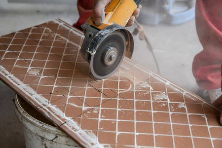 Cutting ceramic tiles. A worker places a large ceramic tile in a cutting machine. Opening a hole in the tile