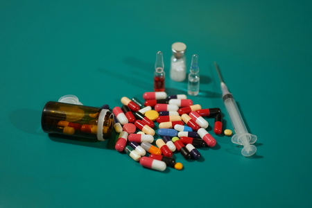 Medication capsules in an opened prescription bottle. Medicine, capsules, tablets, injection, syringe and needle. Close-up of various drugs on green background Фото со стока