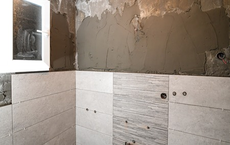 Repair the bathroom. Renovation at home unfinished ceramic tiles with spacers Stock Photo