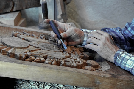 Wood carving. Carver with chisel. A skillful craftsman working on a panel of wood carve decoration