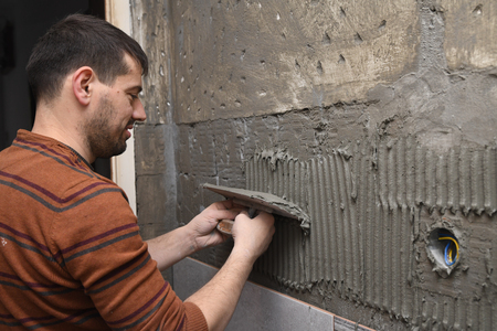 Professional constructor applying glue before laying ceramic tiles on the wall