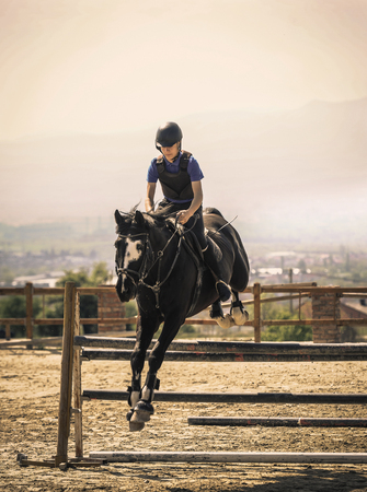 Equestrian sports, Black horse approaching.The jump, shooting from the front. Jockey riding a fast thoroughbred horse
