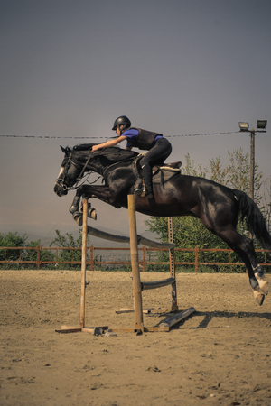 Equestrian sports, Black horse approaching.The jump, shooting from the side. Jockey riding a fast thoroughbred horse