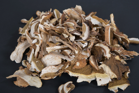 Lot of slices of dry brown mushroom Boletus Edulis. Sliced dried mushrooms on a black background Zdjęcie Seryjne