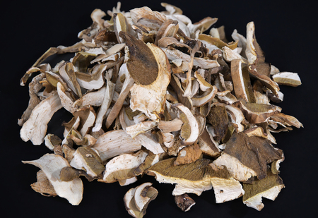 Lot of slices of dry brown mushroom Boletus Edulis. Sliced dried mushrooms on a black background Фото со стока