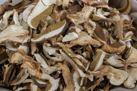 Close up of lot of slices of dry brown mushroom Boletus Edulis. Sliced dried mushrooms on a kitchen table