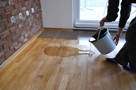 Stripping the varnish parquet from the bucket directly onto the floor Stockfoto