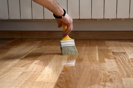 Lackieren Lackieren Parkettboden mit Pinsel - zweite Schicht. Parkett renovieren. Lackpinselstriche auf einem Holzparkett. Auftragen eines hochglänzenden Parkettlacks Standard-Bild