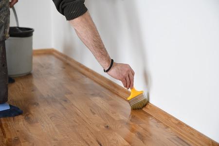 Lakierowanie podłóg drewnianych. Pracownik używa pędzla do powlekania podłóg. Lakierowanie lakierowanie parkietu pędzlem - druga warstwa. Parkiet do renowacji domu Zdjęcie Seryjne