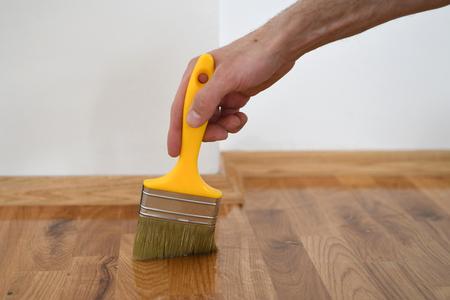 Lackieren von Holzböden. Arbeiter verwendet eine Bürste, um Böden zu beschichten. Lackieren Lackieren Parkettboden mit Pinsel - zweite Schicht. Hausrenovierung Parkett Standard-Bild