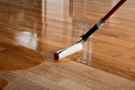Laccatura di pavimenti in legno. Il lavoratore utilizza un rullo per rivestire i pavimenti. Verniciatura laccatura parquet a rullo - secondo strato. Ristrutturazione casa parquet Archivio Fotografico
