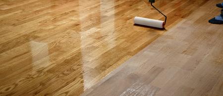Lakierowanie podłóg drewnianych. Pracownik używa wałka do powlekania podłóg. Lakierowanie lakierowanie parkietu wałkiem malarskim - druga warstwa. Parkiet do renowacji domu