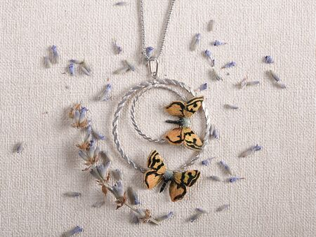Handmade copper jewelry in the shape of butterfly from the genus Orgyia dubia. Handmade jewelry