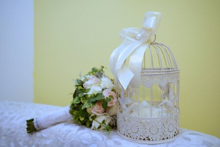 Wedding reception table closeup with details and decorations including flowers. Decorative vintage white bird cage