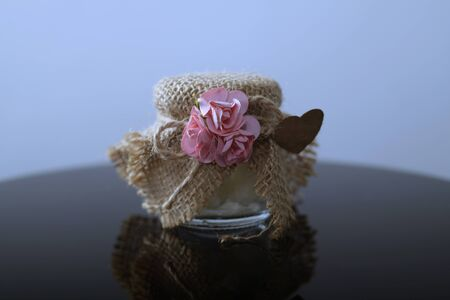 Natural honey homemade sweet in glass jar. Healthy natural product. Small glass jar with metal cap covered with rough linen jute, sackcloth piece