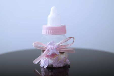 Small baby bottle with nipple with decorations and rose ribbon. Newborn stile
