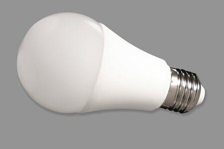 Led bulb light and energy-saving lamp on table on gray background. Energy saving concept Reklamní fotografie