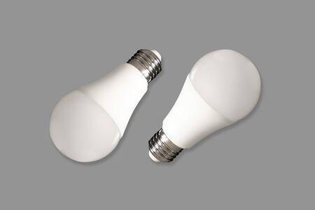 Two led bulb lights and energy-saving lamps on table on gray background. Energy saving concept
