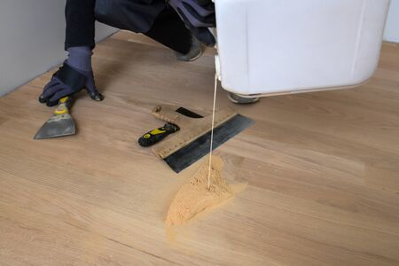 Master parquet with glue bin in your hand. Preparation of parquet grout material. Mixing retainer, varnish and a small mixture of wood. Pre-varnishing phase