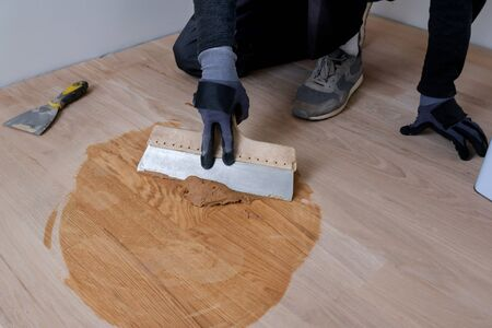 Master parquet with spatula in your hand. Preparation of parquet grout material. Mixing retainer, varnish and a small mixture of wood. Pre-varnishing phase