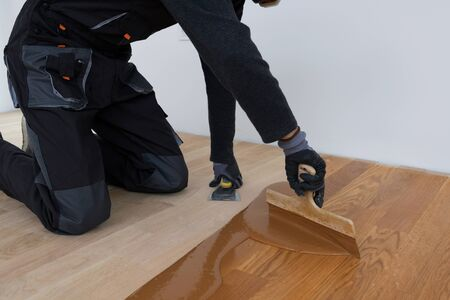 Carpenter master with gloves grouting wooden parquet, phase after sanding. Varnishing of oak parquet floor, man workers with hand and spatula