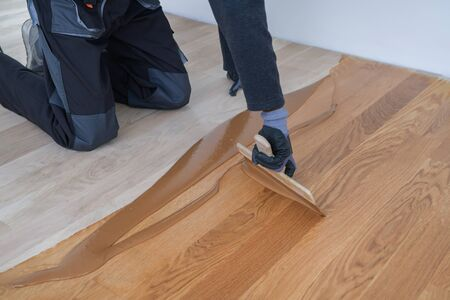 Carpenter master with gloves grouting wooden parquet, phase after sanding. Varnishing of oak parquet floor, man workers with hand and spatula Imagens