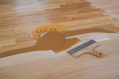 Mix of wood dust, wood varnish, hardener and other parquet varnishes, spatula on the floor
