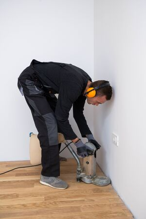Scraping floor surface with grinding machine. Repair in the apartment. Carpenter grinder parquet in a narrow corner with a small machine Banque d'images - 135108459