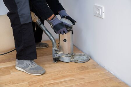 Scraping floor surface with grinding machine. Repair in the apartment. Carpenter grinder parquet in a narrow corner with a small machine Banque d'images - 135108424