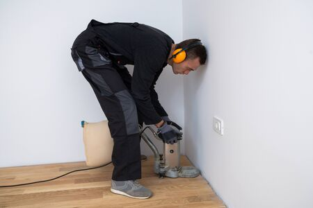 Scraping floor surface with grinding machine. Repair in the apartment. Carpenter grinder parquet in a narrow corner with a small machine