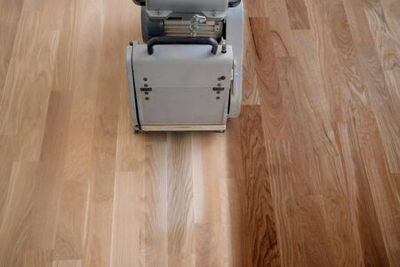 Scraping hardwood floor with the grinding machine. Repair in the apartment. Carpenter doing parquet wood floor polishing maintenance work by grinding machine Banque d'images - 135108444
