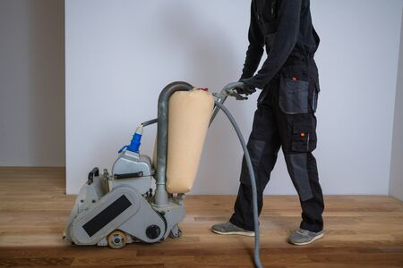 Scraping hardwood floor with the grinding machine. Repair in the apartment. Carpenter doing parquet wood floor polishing maintenance work by grinding machine Banque d'images - 135108422