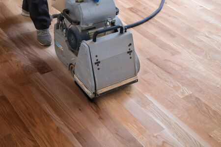 Scraping hardwood floor with the grinding machine. Repair in the apartment. Carpenter doing parquet wood floor polishing maintenance work by grinding machine Banque d'images - 135108451