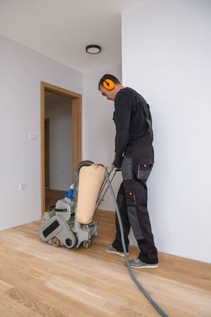 Scraping hardwood floor with the grinding machine. Repair in the apartment. Carpenter doing parquet wood floor polishing maintenance work by grinding machine Banque d'images - 135108426