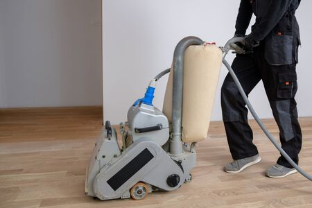 Scraping hardwood floor with the grinding machine. Repair in the apartment. Carpenter doing parquet wood floor polishing maintenance work by grinding machine