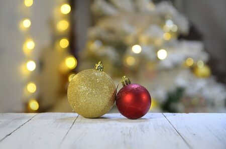 Various Christmas decorations. Christmas balls decoration on white wooden surface. Golden and red Christmas balls