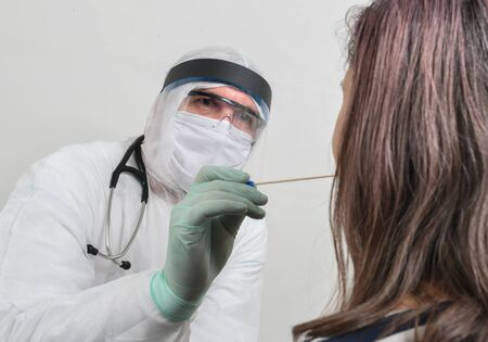 Male doctor examining her female patient with stick to make swab test. Young handsome woman visiting young male doctor epidemiologist