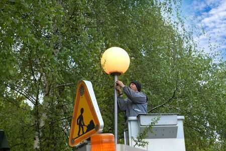 Worker in lift bucket repair street light. People change the lamp on a street lamp Stock fotó