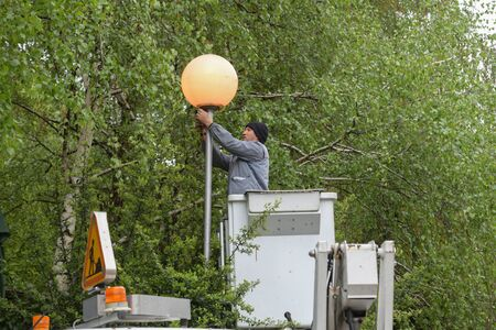 Worker in lift bucket repair street light. People change the lamp on a street lamp Stock Photo